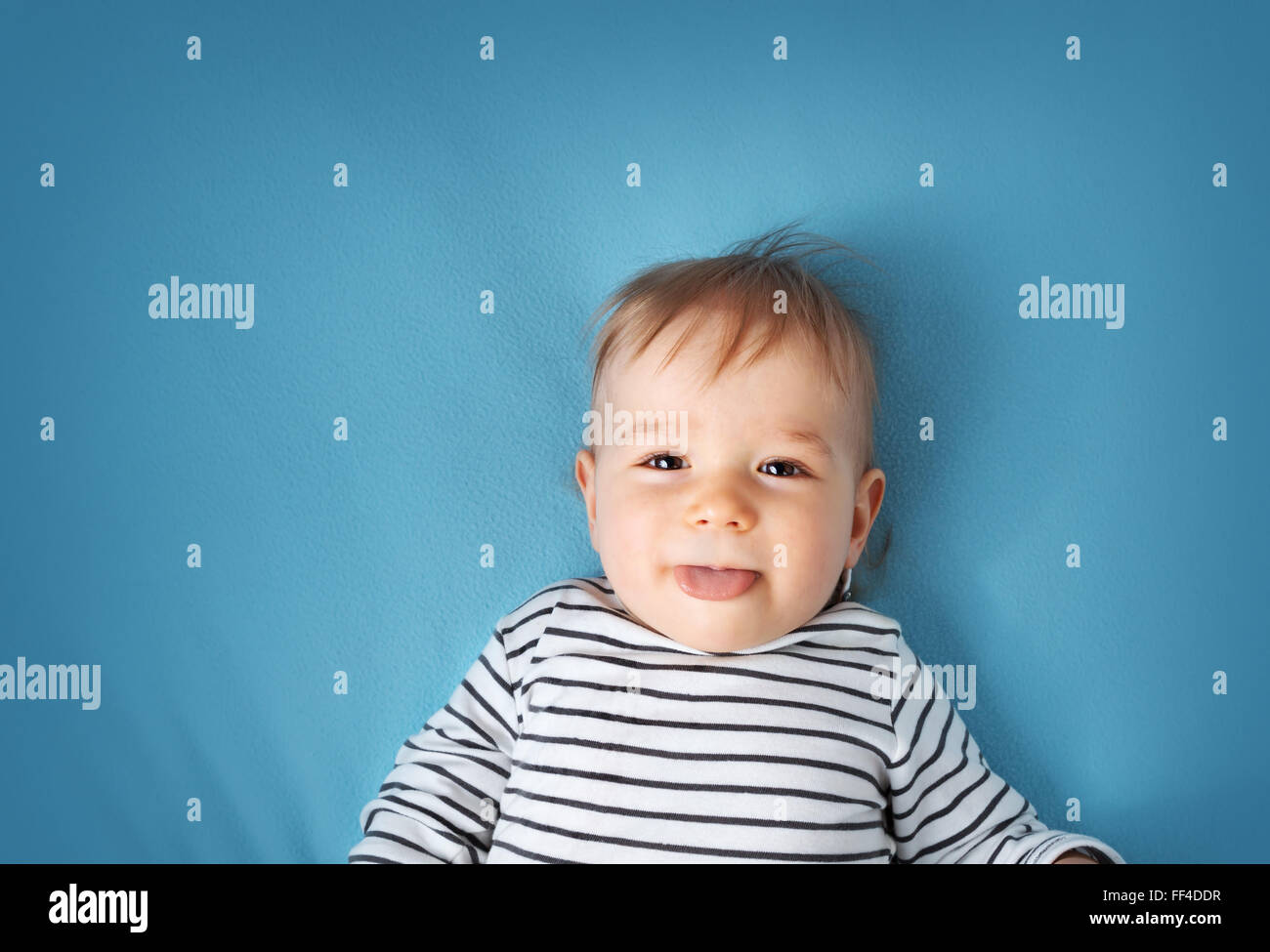 little boy on blue blanket background Stock Photo