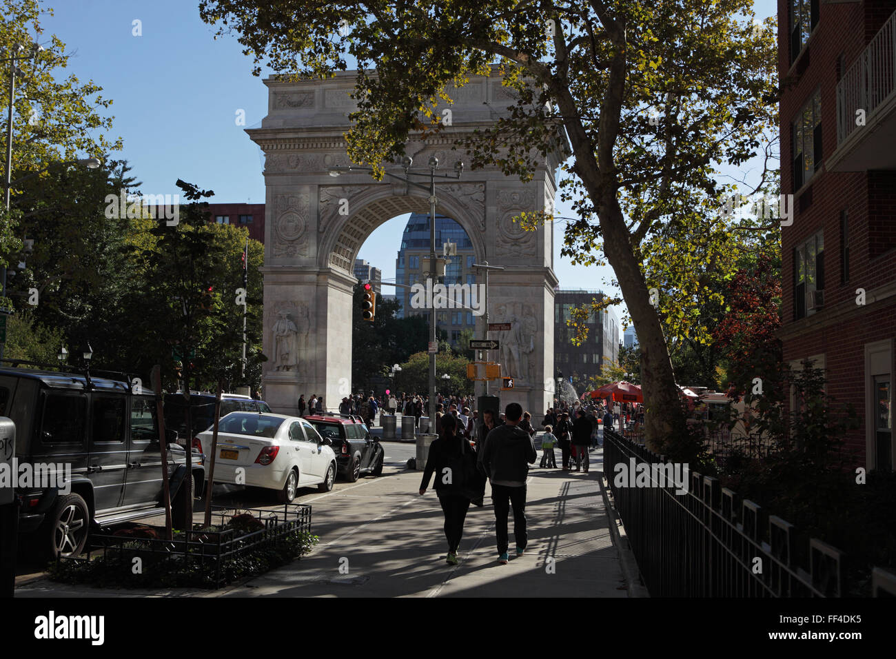 People walk south down Fifth Avenue into Washington Square Park on a warm autumn day - Stock Image