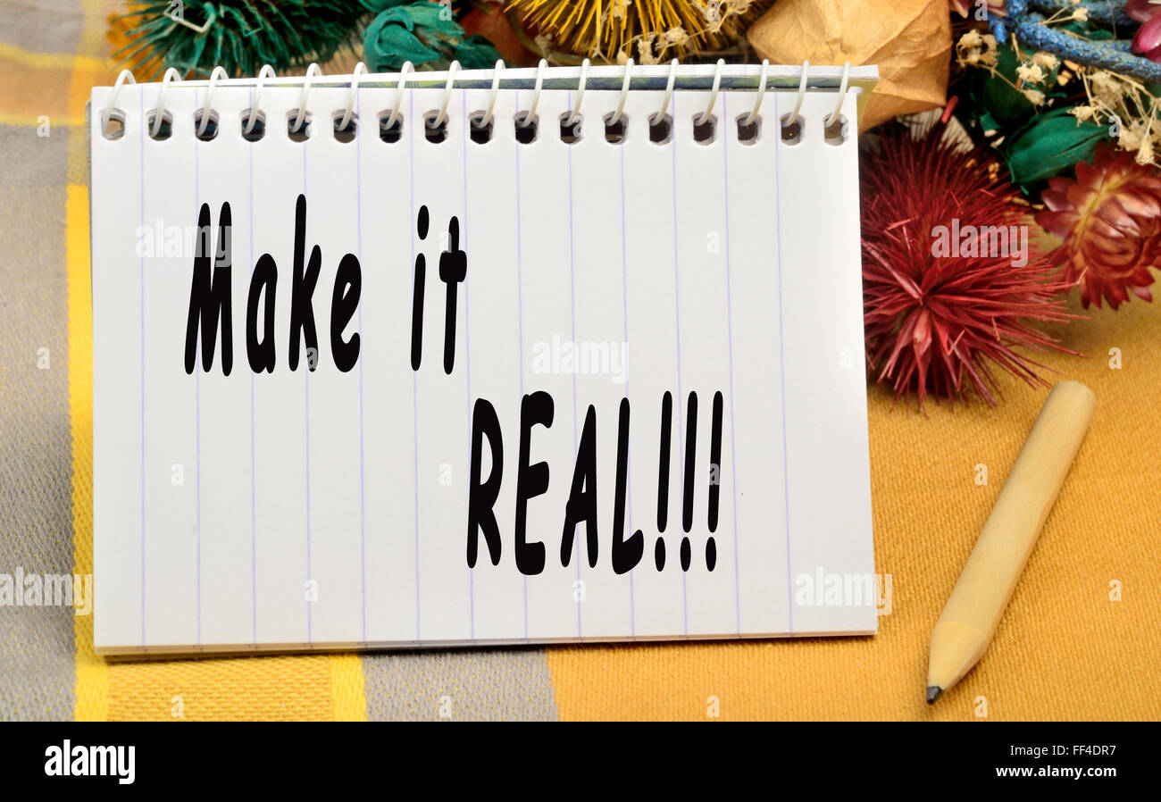 Make it real written on notebook - Stock Image