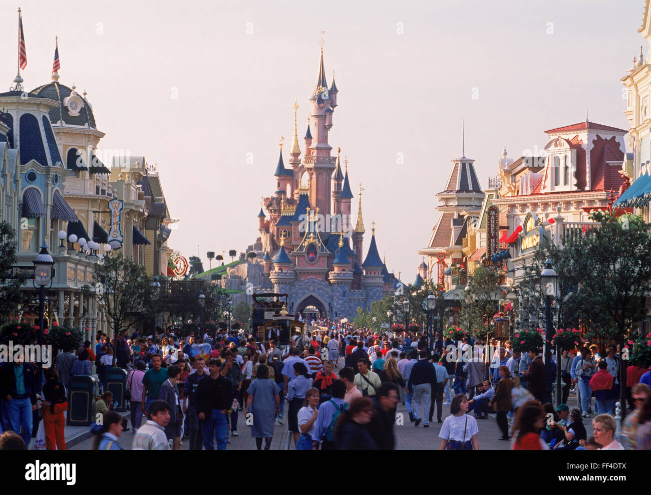 The Castle with Main Street shops, rides and people during daytime at Euro Disneyland at Euro Disney Resort outside - Stock Image