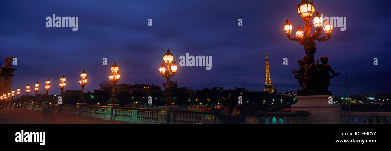 Romantic lamp lights at night in Paris across Pont Alexandre III with Eiffel Tower, - Stock Image