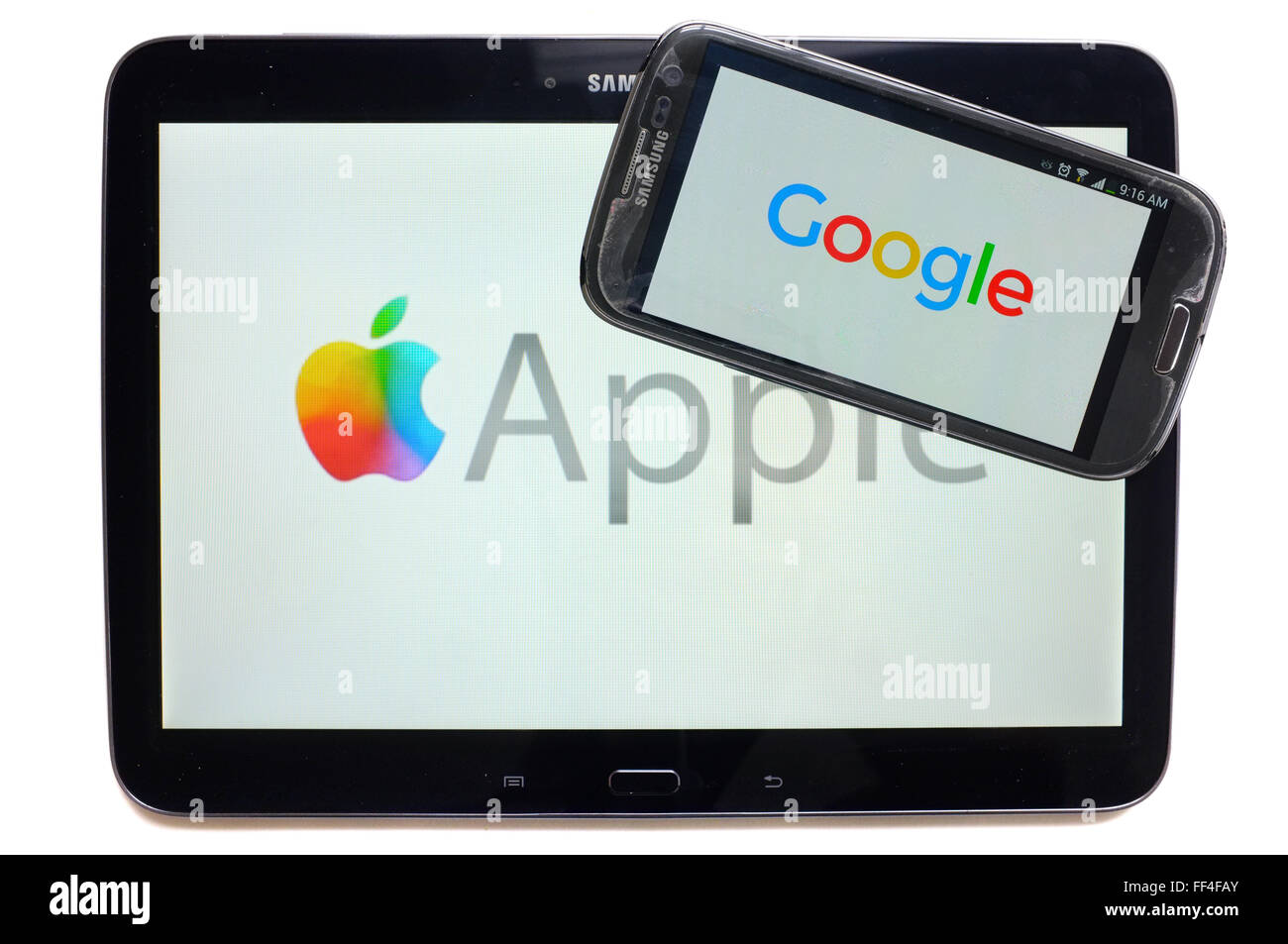 The Google logo on a smartphone and Apple on a tablet photographed against a white background. - Stock Image