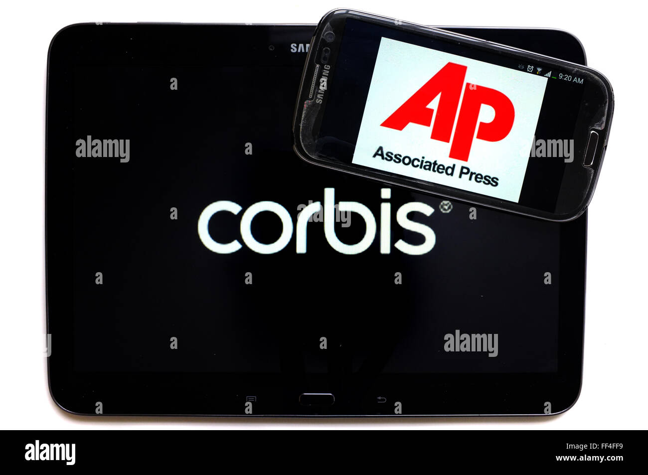 The Corbis logo on a smartphone and Associated Press on a tablet photographed against a white background. - Stock Image