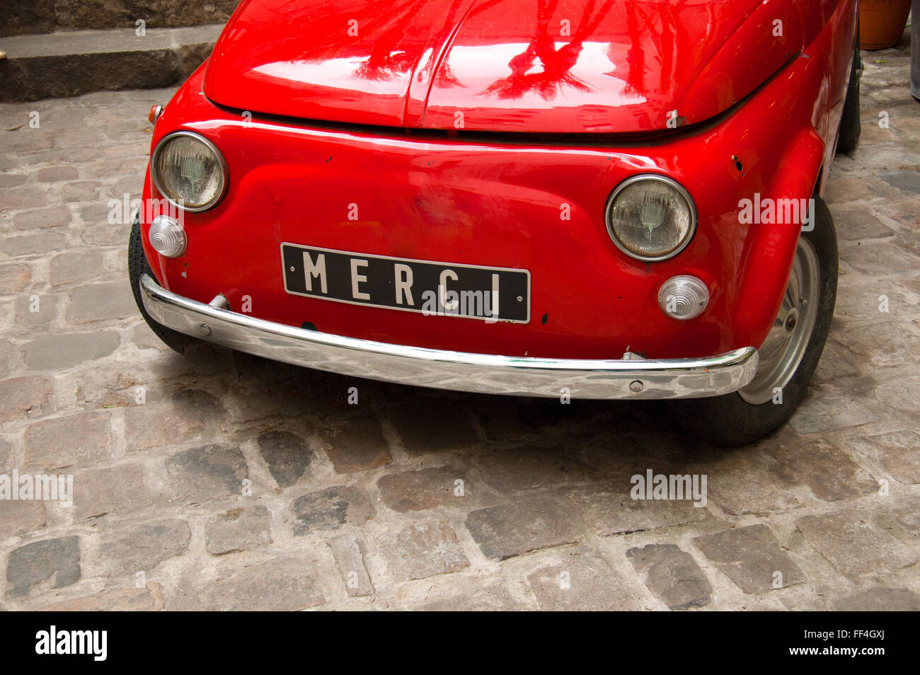 Old vintage Italian car in red with Merci written on the plate - Stock Image
