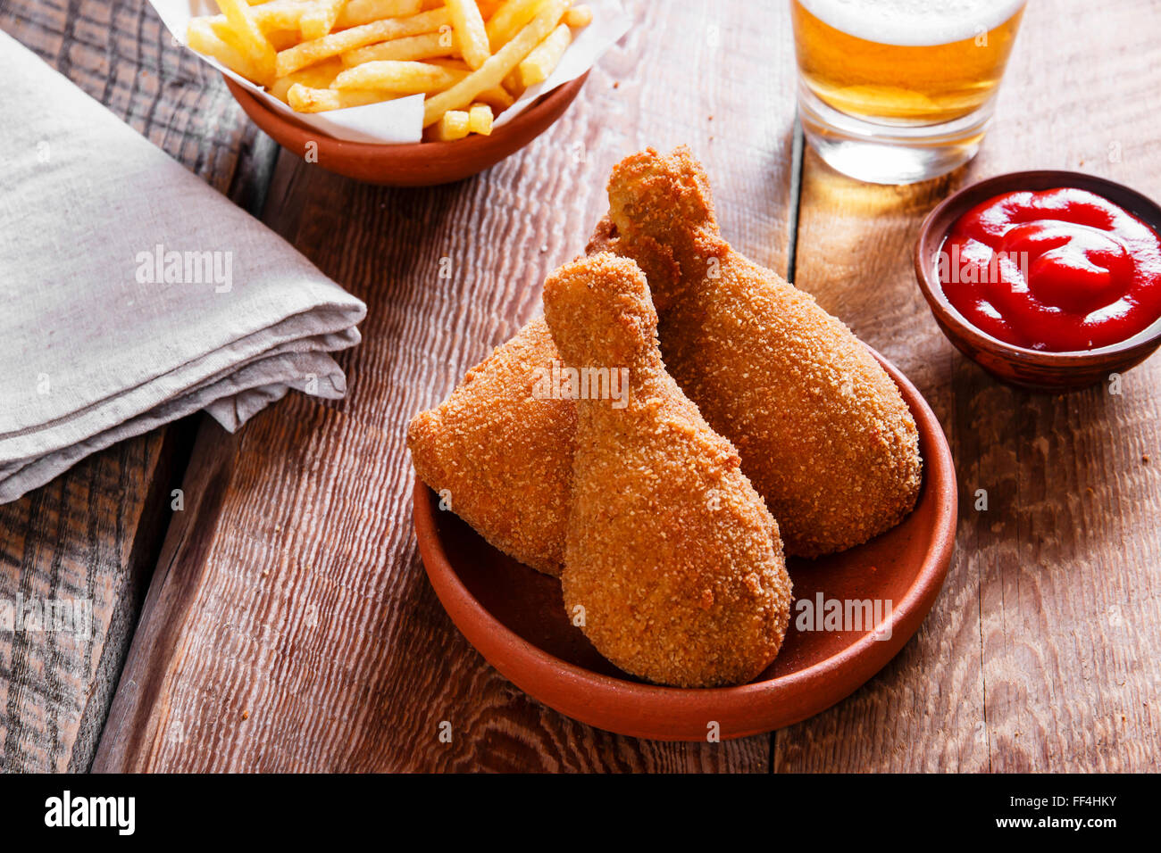 fried chicken leg in breadcrumbs and french fries - Stock Image