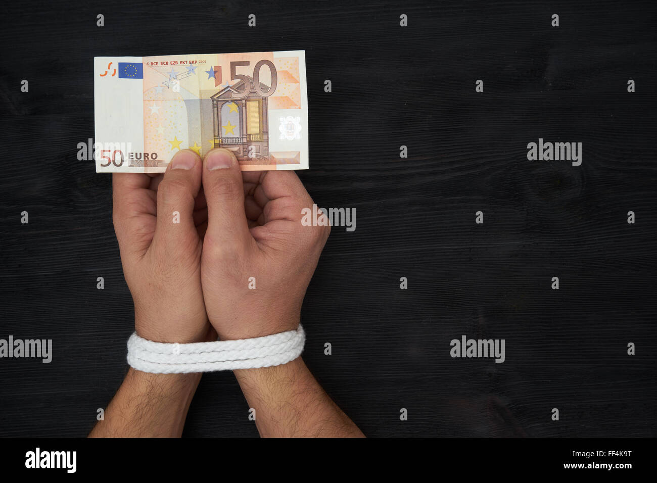 Prisoner of profit - man holding money with hands tied up - Stock Image