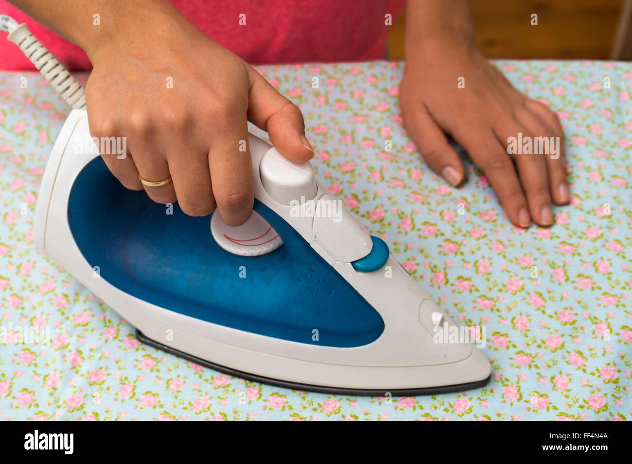 Woman ironing sheet with flowers - Stock Image