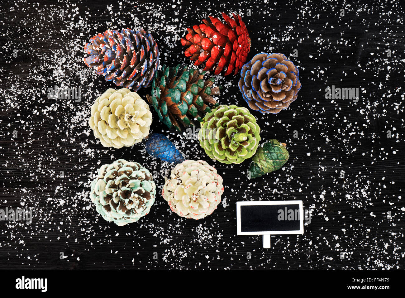 Pinecones painted with different paints, isolated on black background - Stock Image