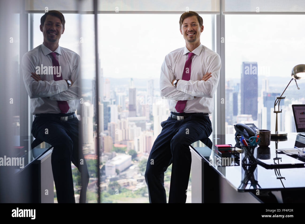 Adult businessman sitting in modern office with beautiful sight of the city. The man looks at the camera and smiles - Stock Image