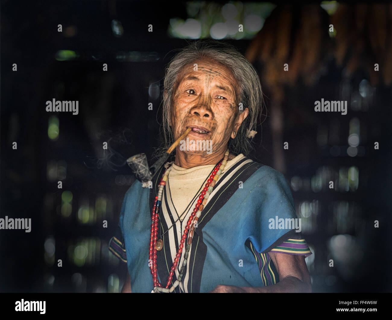 A Muun Chin woman with face tattoos smoking a corncob pipe, Kyar Daw, Mindat, Myanmar. - Stock Image