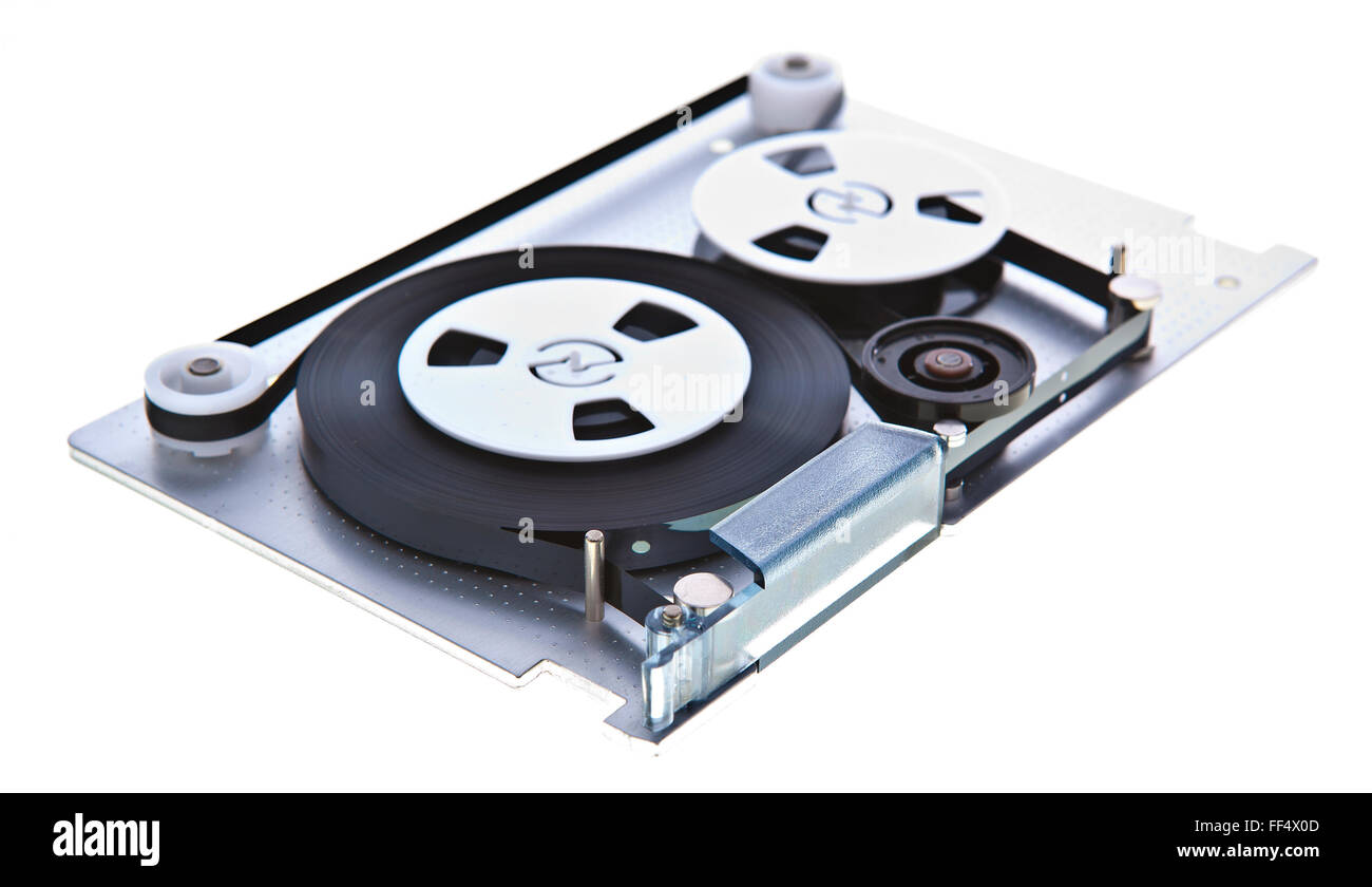 Old Computer tape taken apart on a white background - Stock Image