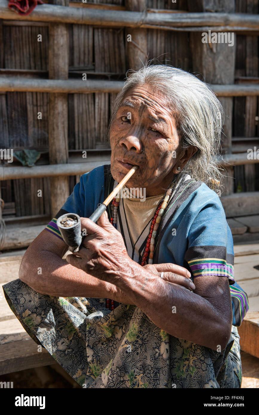A Muun Chin woman with face tattoos smoking a corncob pipe, Kyar Daw, Mindat, - Stock Image