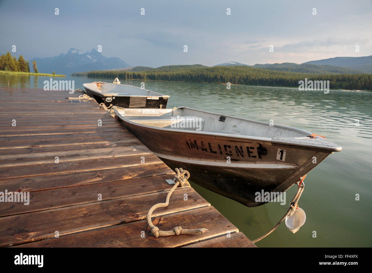 Evening light over Jasper National Park's Maligne Lake and boats available for rent at the historic Curly Phillips - Stock Image