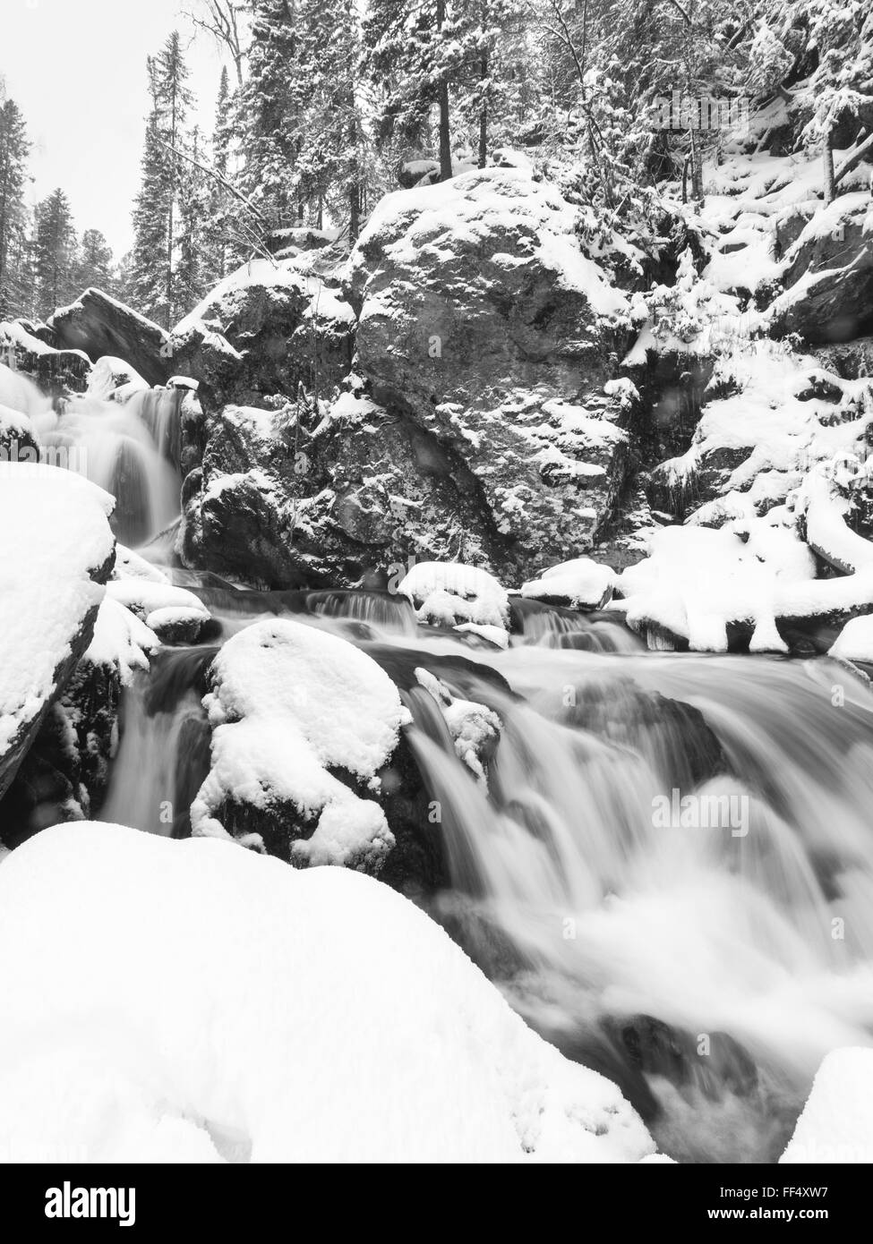 waterfall in snow, frozen waterfall, snowy cold water of north river, russian nature - Stock Image