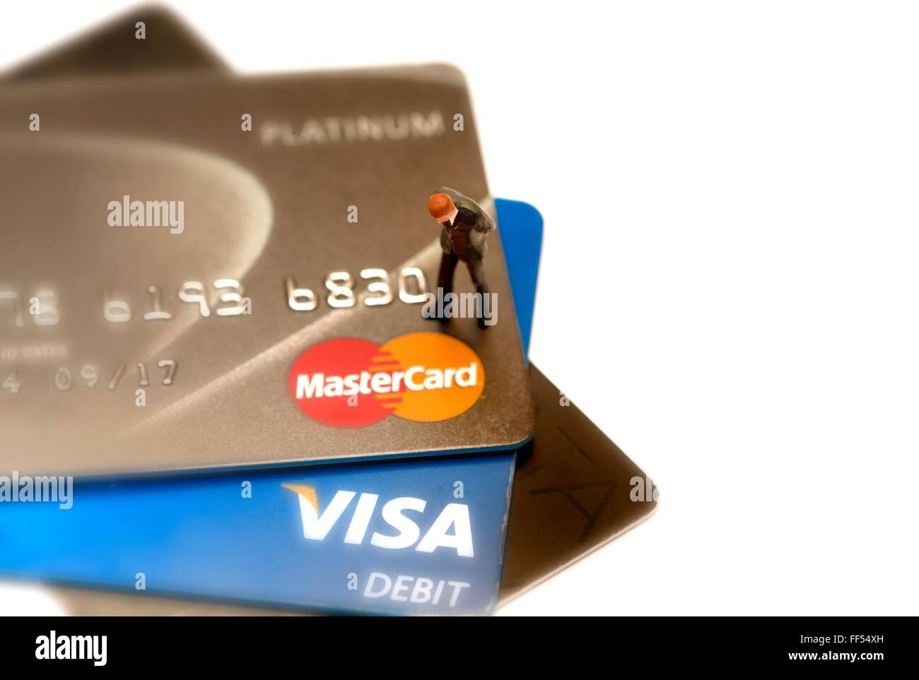 A Debit and credit card close up with a miniature figurine standing looking down - Stock Image
