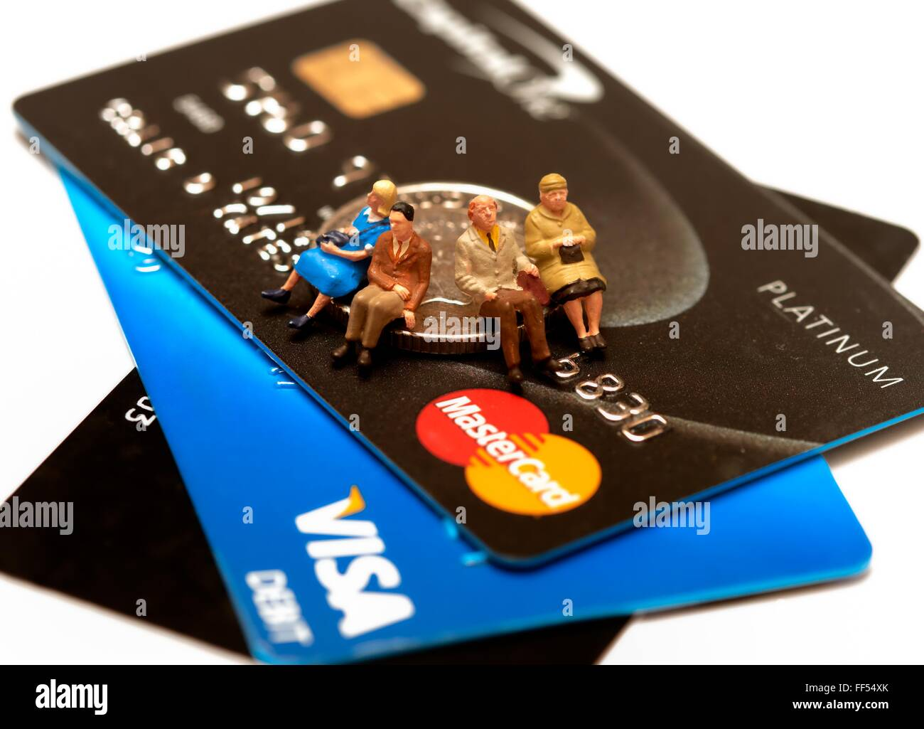 A Debit and credit card close up with a miniature figurines sitting on a coin. - Stock Image