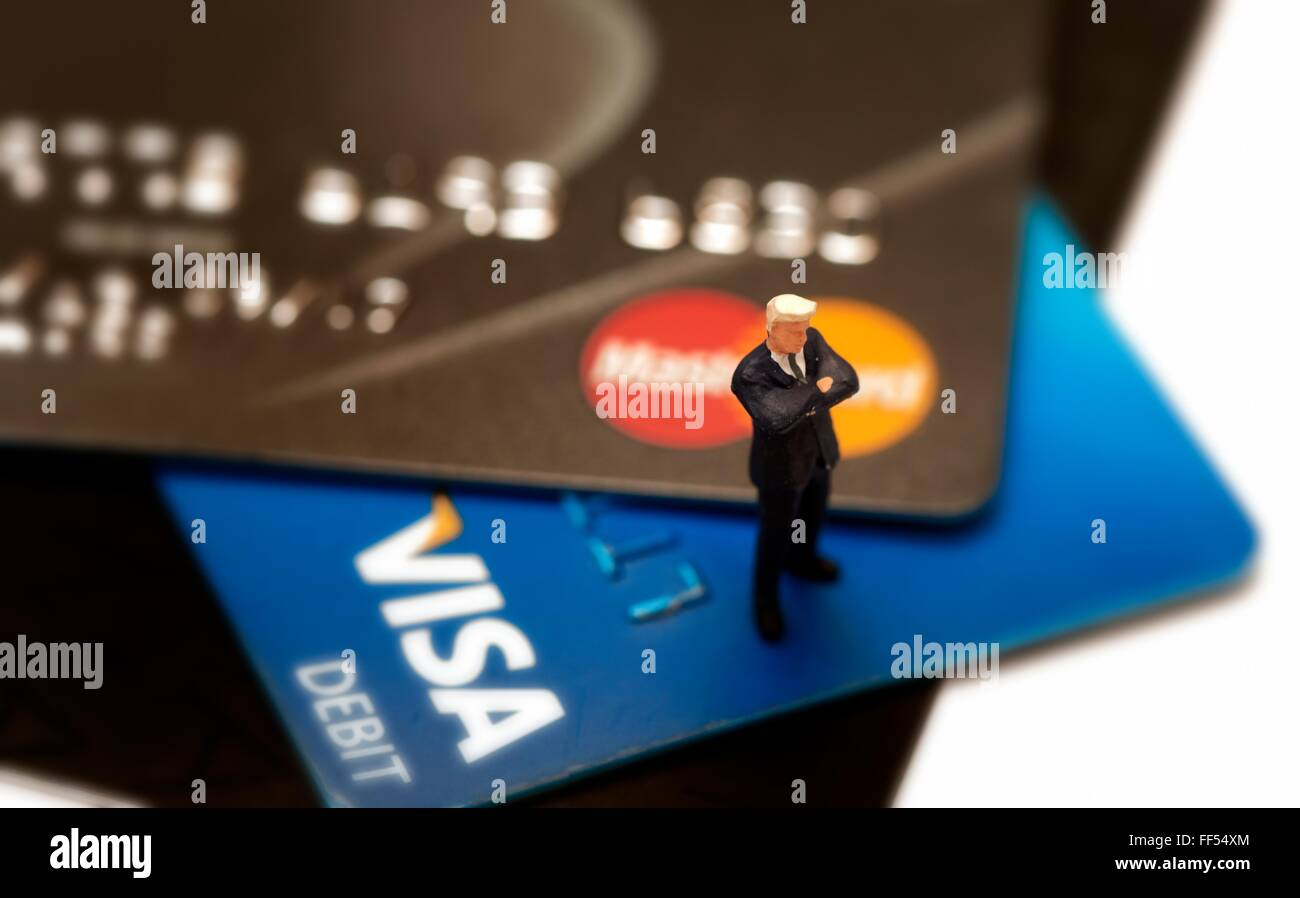 A Debit and credit card close up with a miniature figurine standing arms folded. - Stock Image