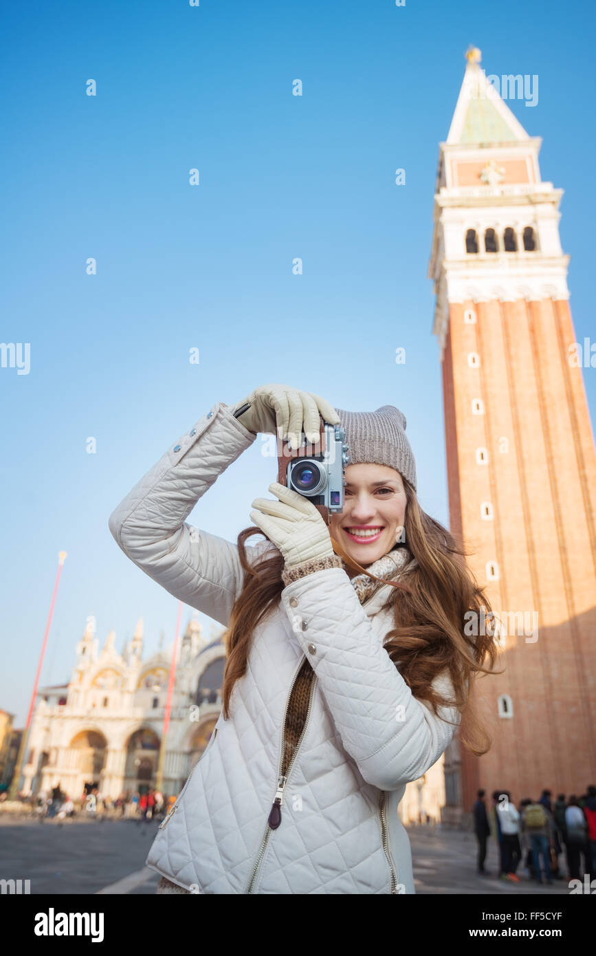 Take classical tourist enjoyment in Venice, Italy - wander over San Marco square, chase pigeons and take photos. - Stock Image
