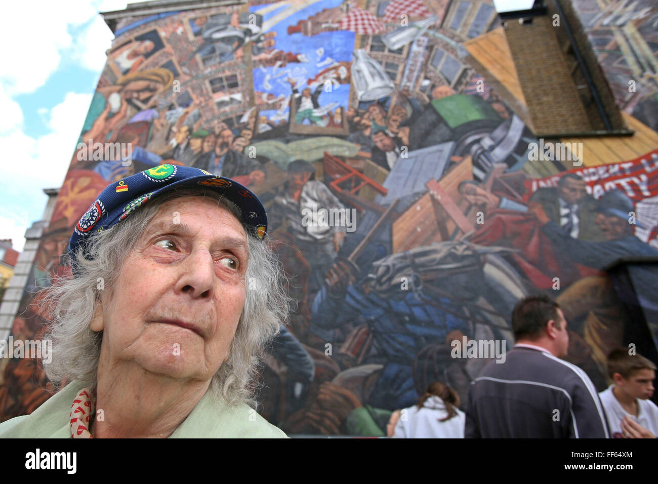 Mrs Betty Papworth a veteran peace campaigner stands in front of the Cable Street mural on the 70th anniversary - Stock Image