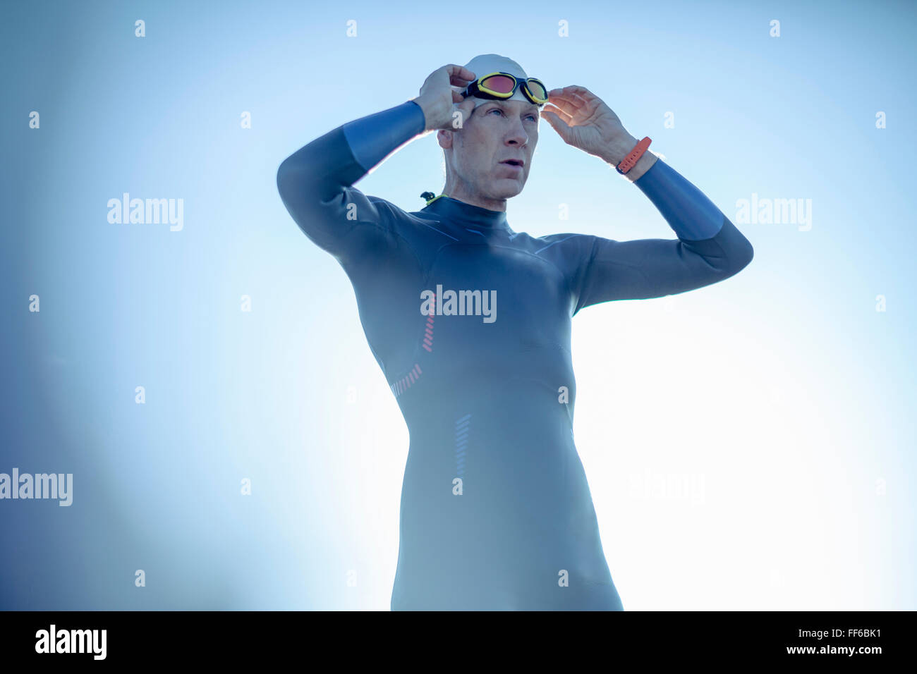 A swimmer in a wetsuit and swimming hat, adjusting his swimming goggles. - Stock Image