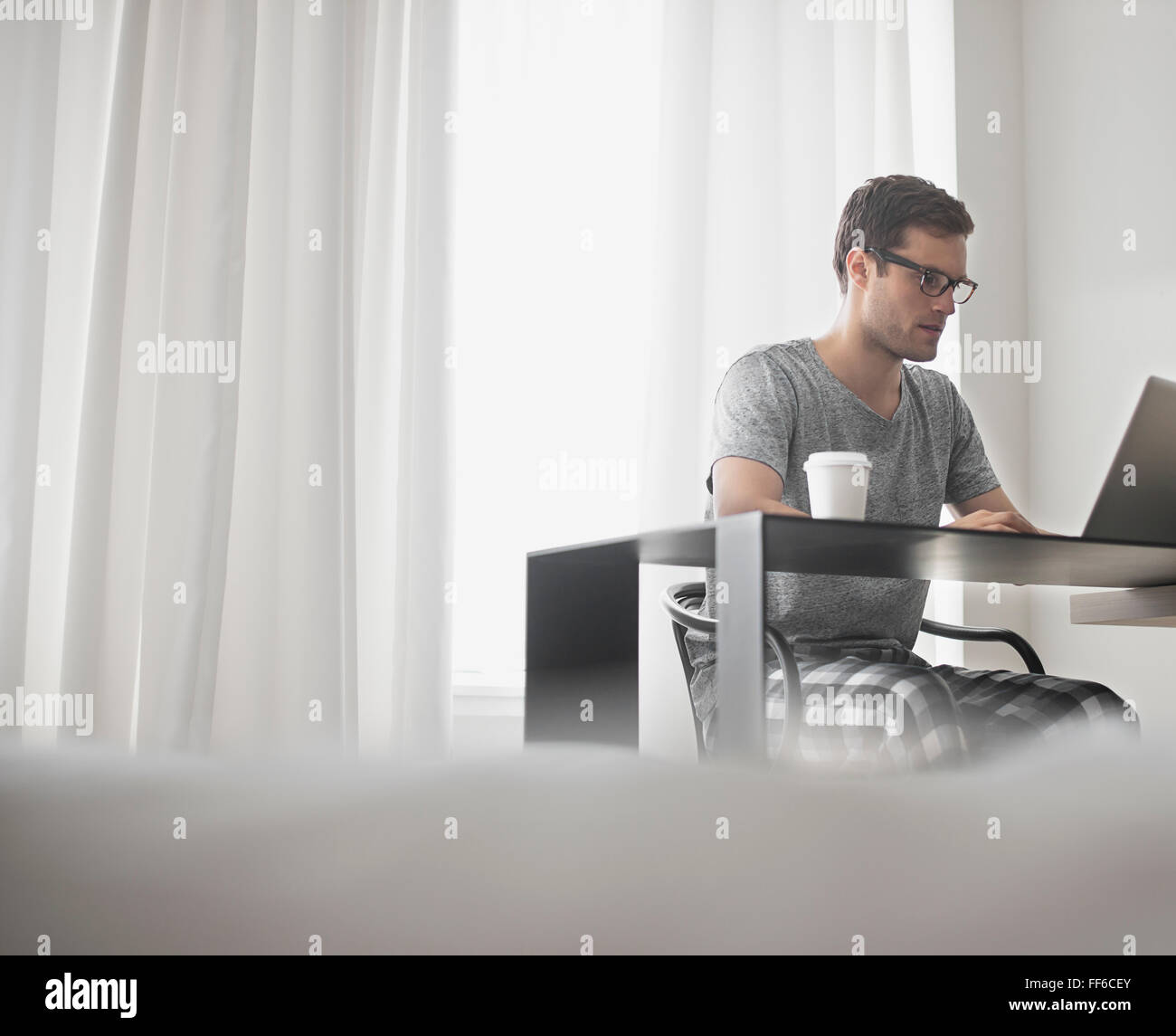A working day. A man seated at a laptop computer, working in a hotel bedroom with a cup of coffee. Stock Photo