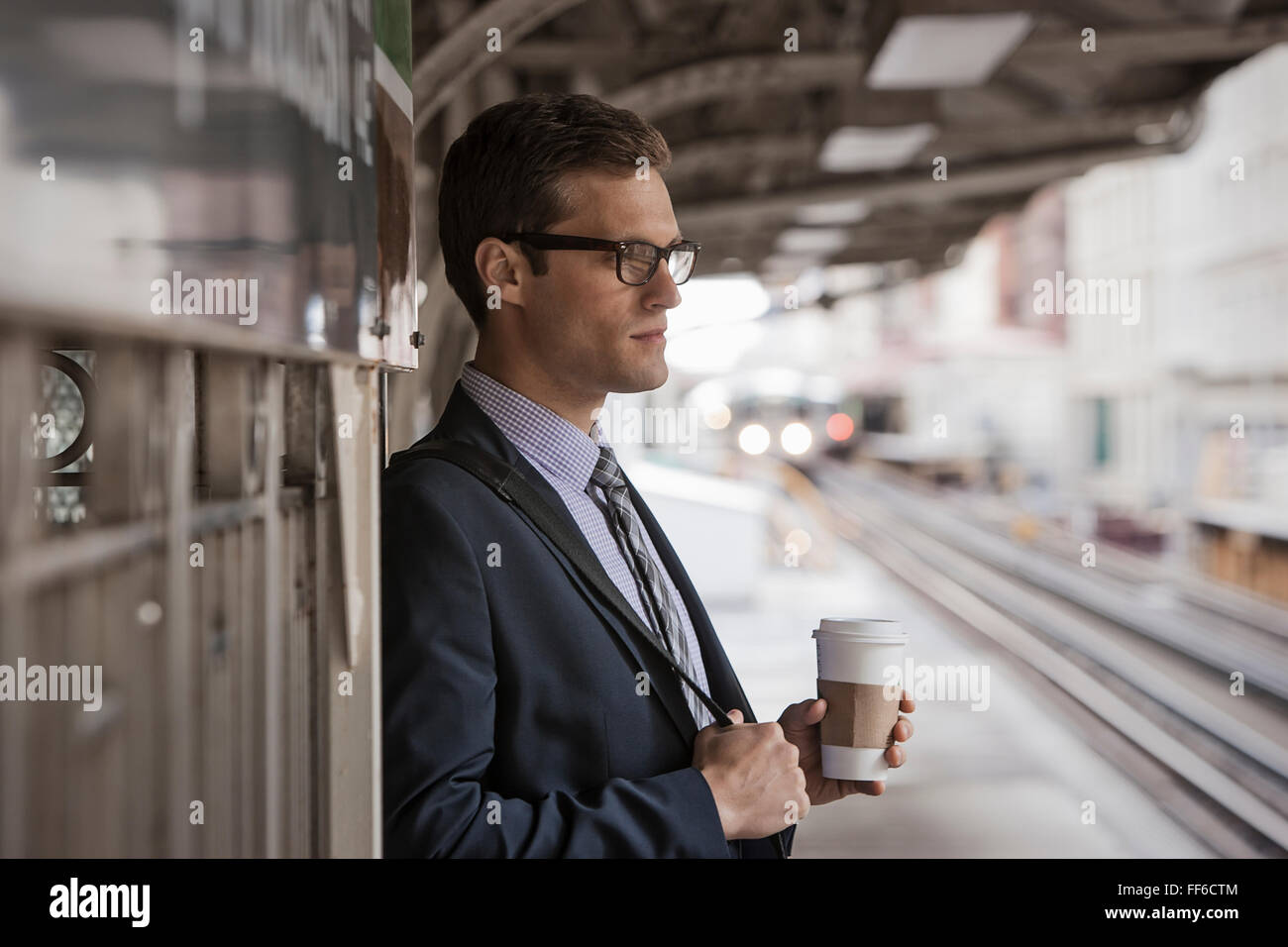 A working day. Businessman in a work suit and tie holding a cup of coffee on a railway platform. - Stock Image