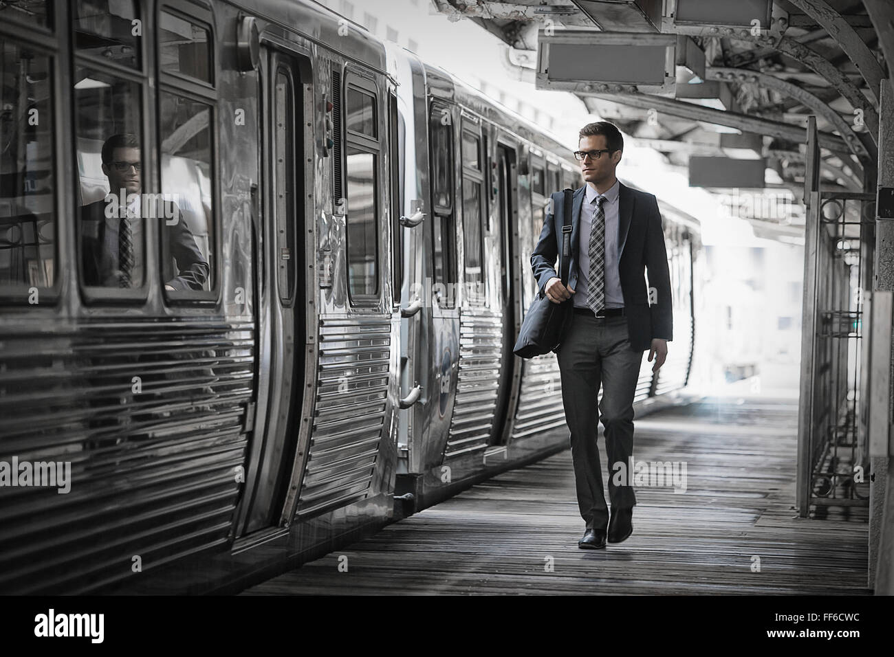 A working day. Businessman in a work suit and tie walking on the platform by a train carriage. - Stock Image