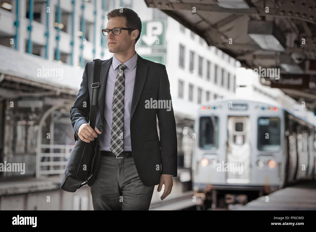 A working day. Businessman in a work suit and tie on a railway station platform. - Stock Image