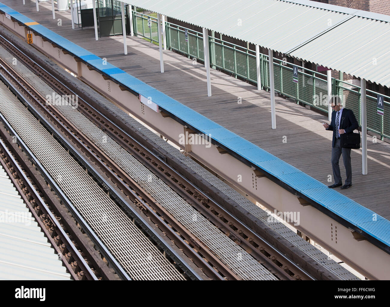 A working day. A view down on a railway station and a man waiting on the platform. - Stock Image