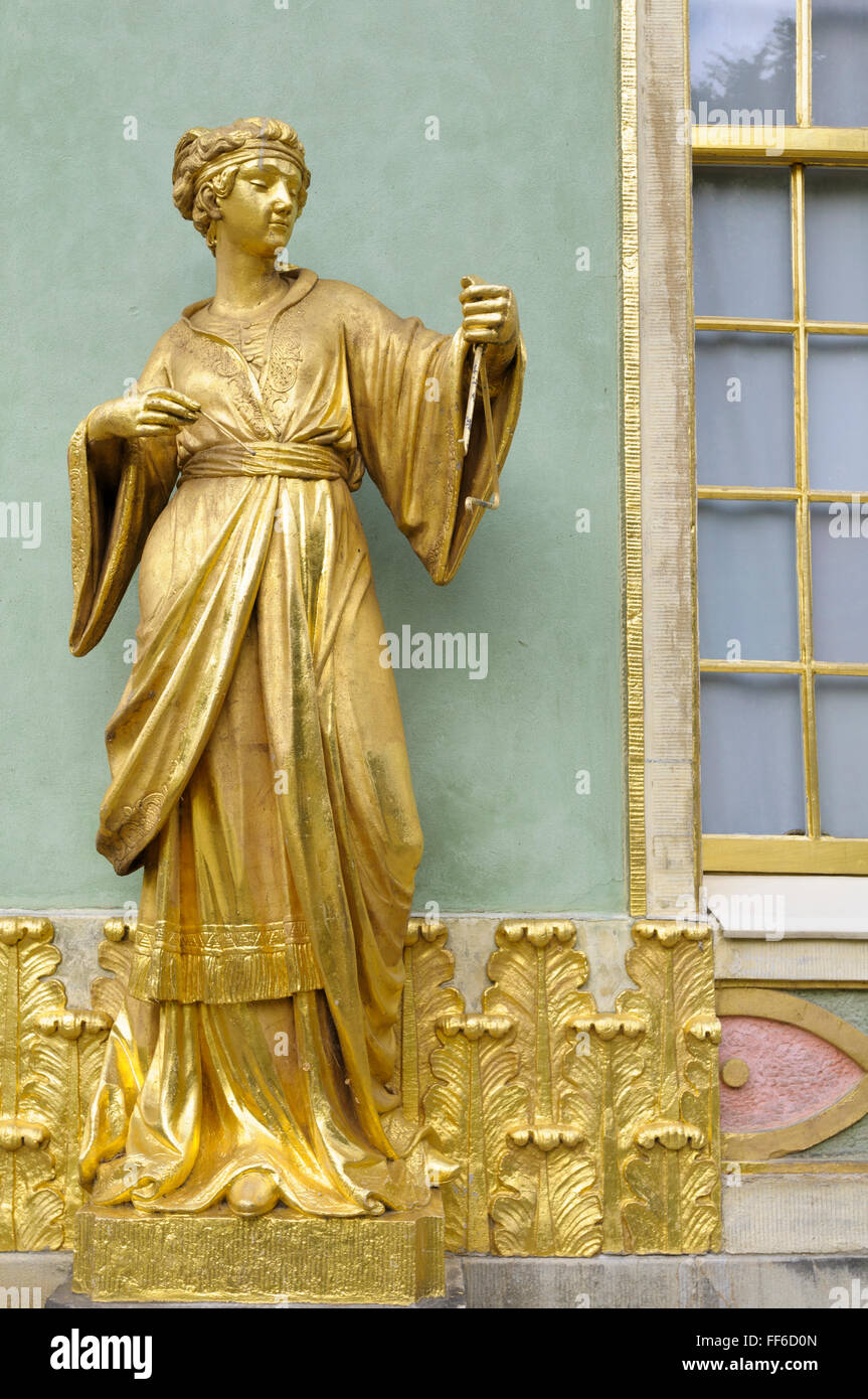 Gilded sandstone statue of a woman playing the triangle, Chinese House, Sanssouci Park, Potsdam, Germany - Stock Image
