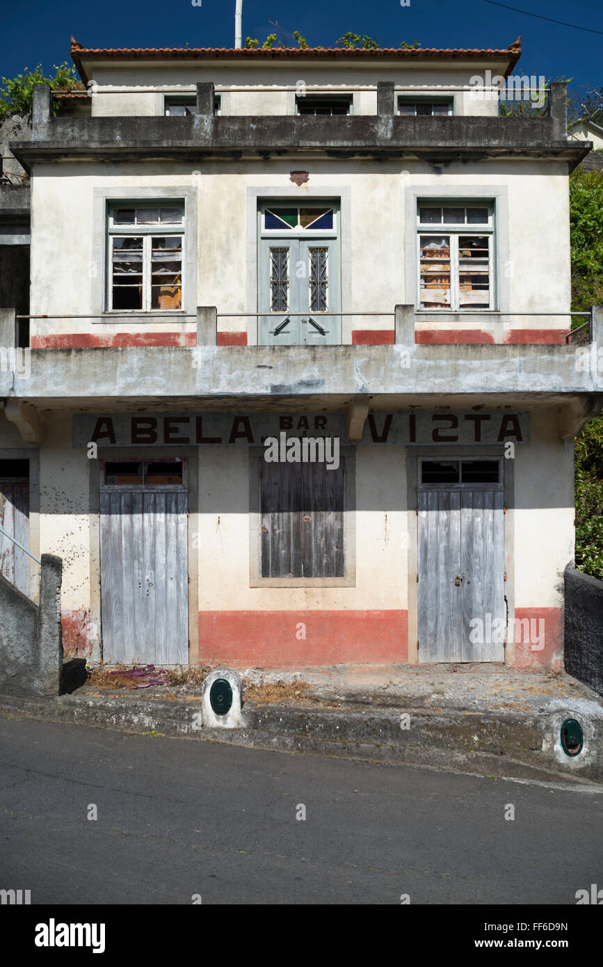 Facade with door and window if decaying shabby house with vacate closed bar and restaurant in a small village on - Stock Image