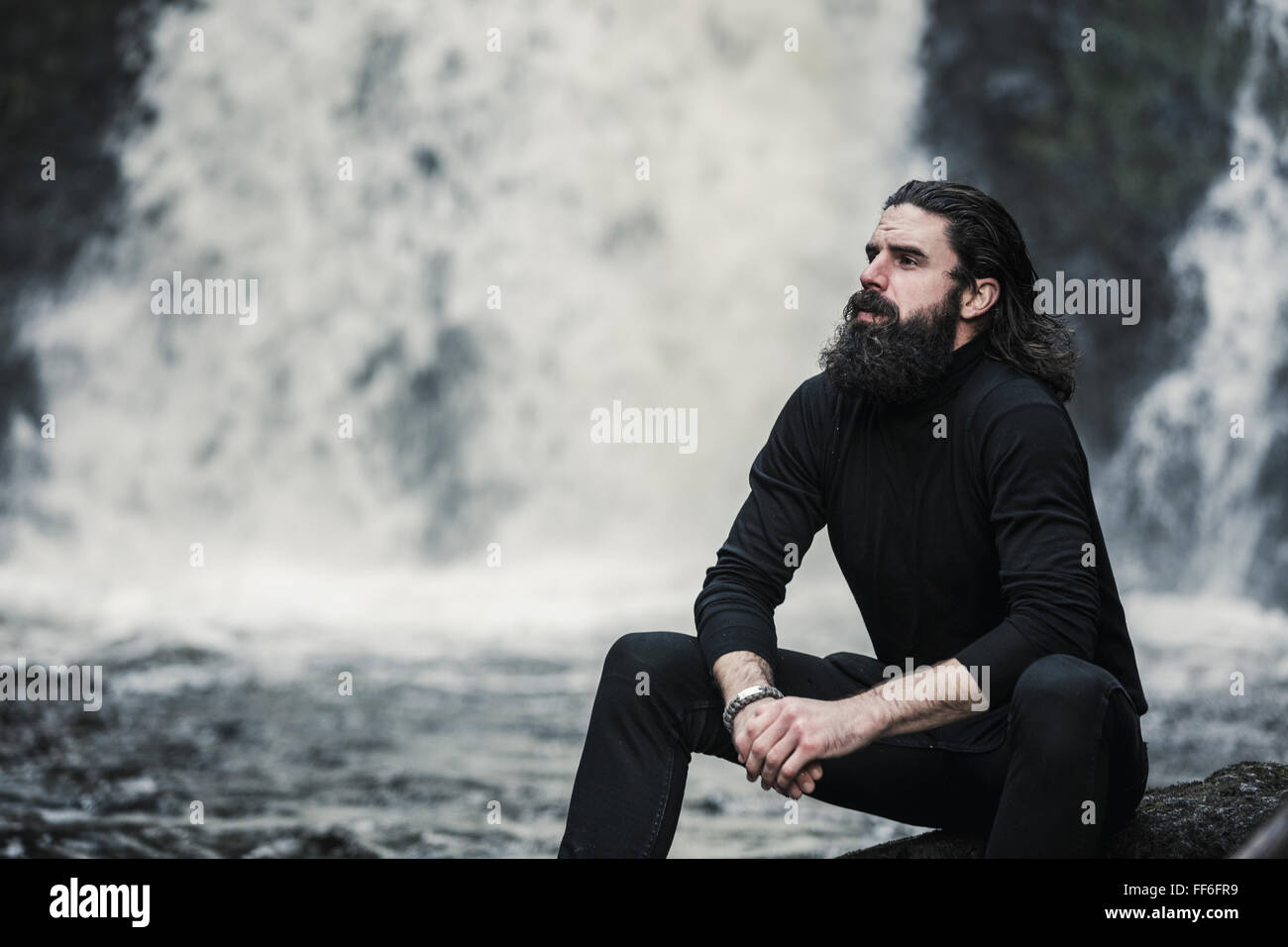 A man sitting with his hands clasped looking up, by a cascade of water, a mountain stream. - Stock Image