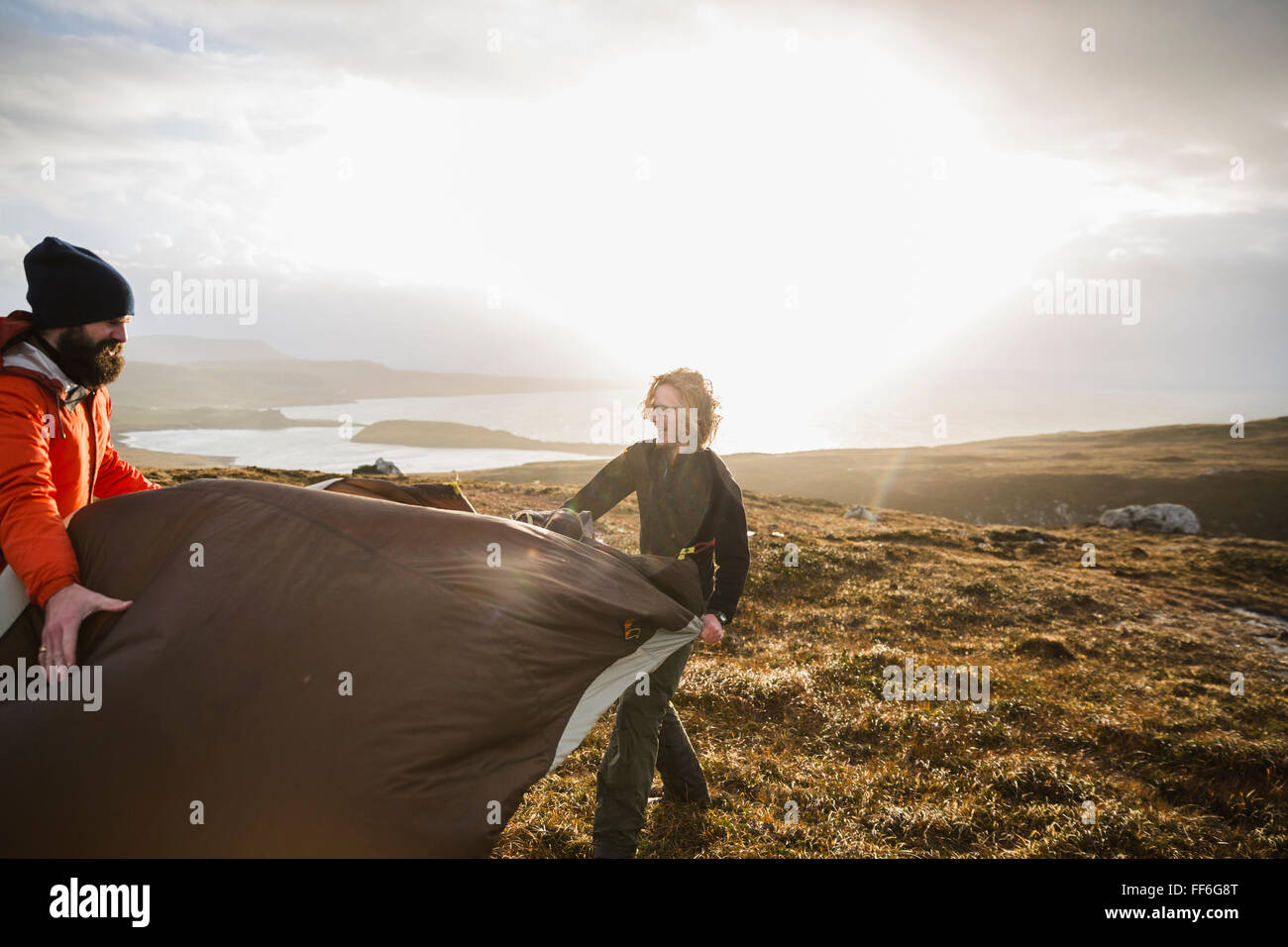 Two men holding and putting up a small tent in open space. Wild camping. - Stock Image