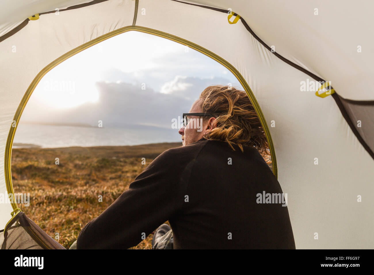 A man sitting in the shelter of a tent looking out. - Stock Image