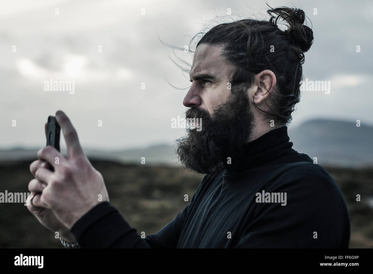 A man taking a photograph with a smart phone. - Stock Image