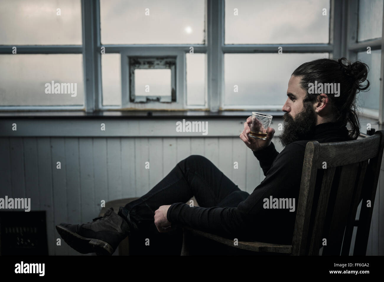 A man sitting looking at the view out of a window, drinking from a glass. - Stock Image