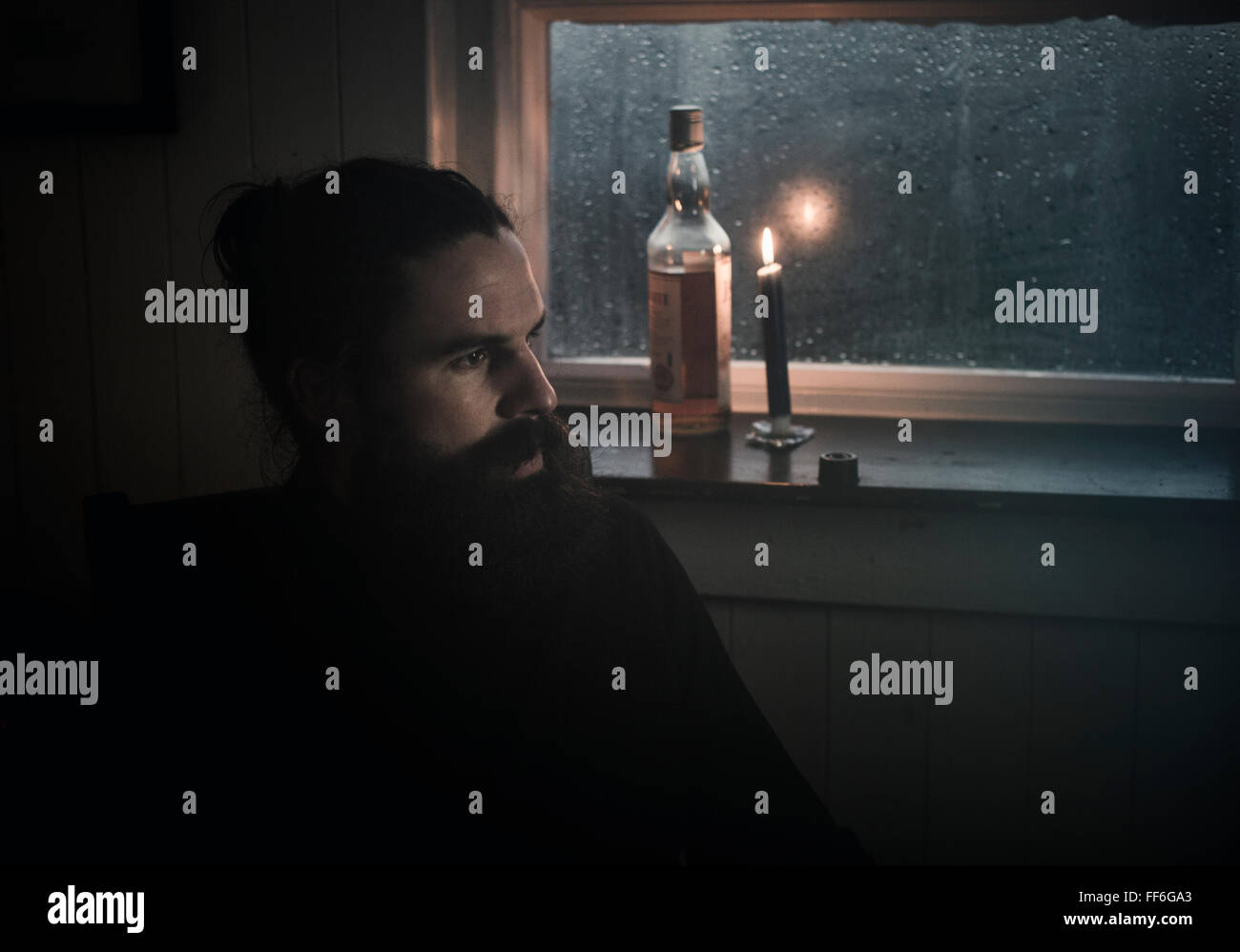 A man sitting in the dark by a window in candlelight drinking from a small glass.  A bottle beside him. - Stock Image
