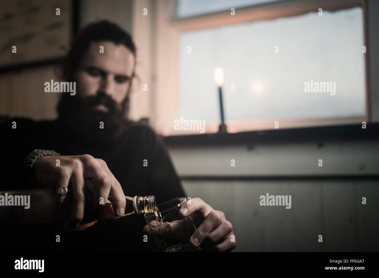 A man sitting alone in a room pouring himself a glass of whisky. A lit candle. - Stock Image