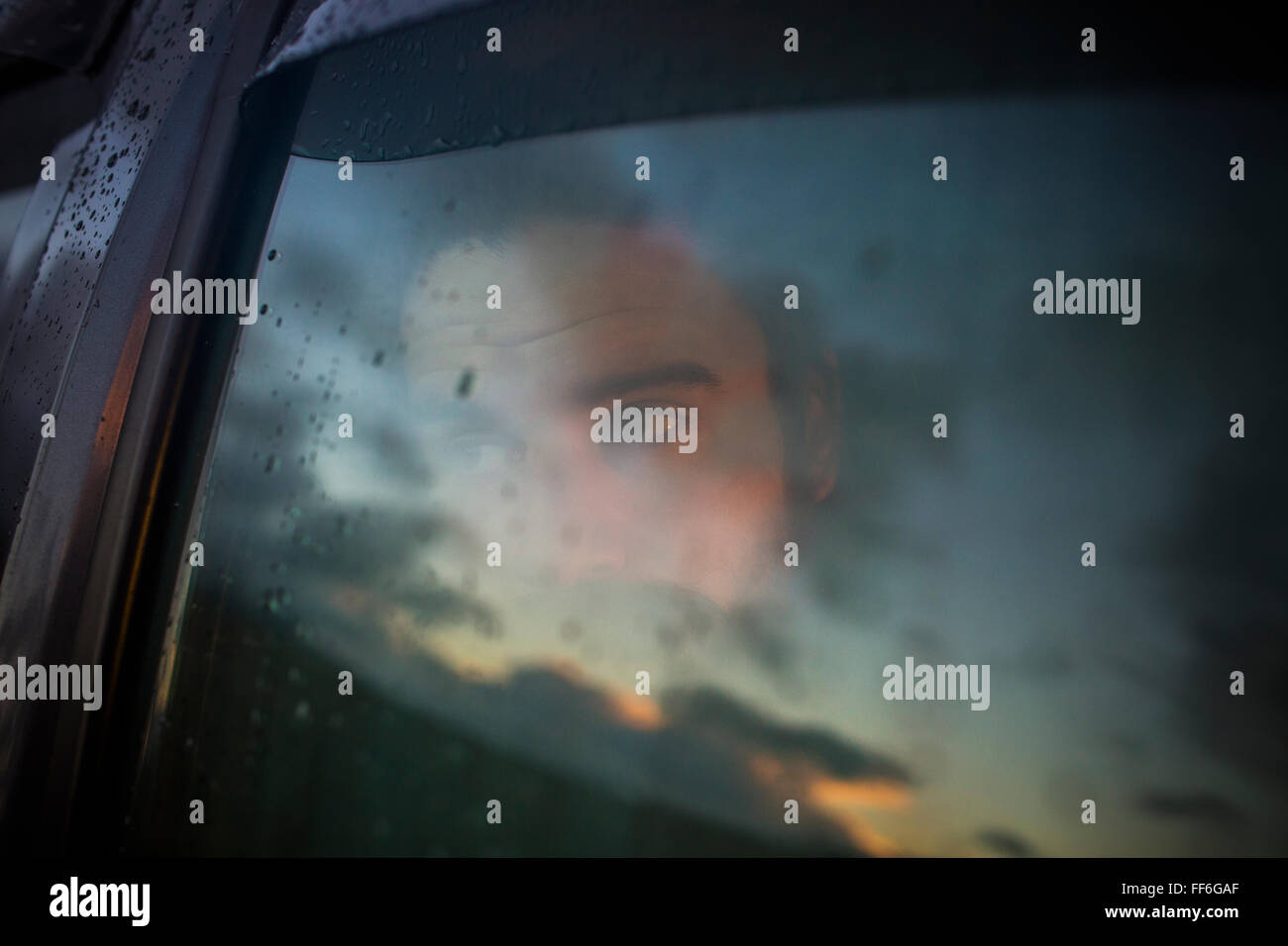 A man sitting in a car looking out. Reflections of the sunset sky on the window. - Stock Image