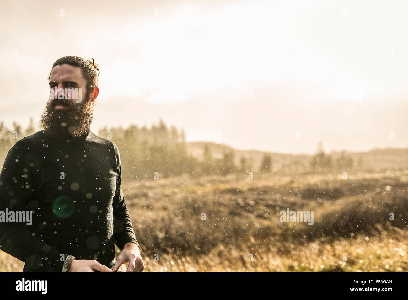 A man standing in sunlit open country in winter. - Stock Image
