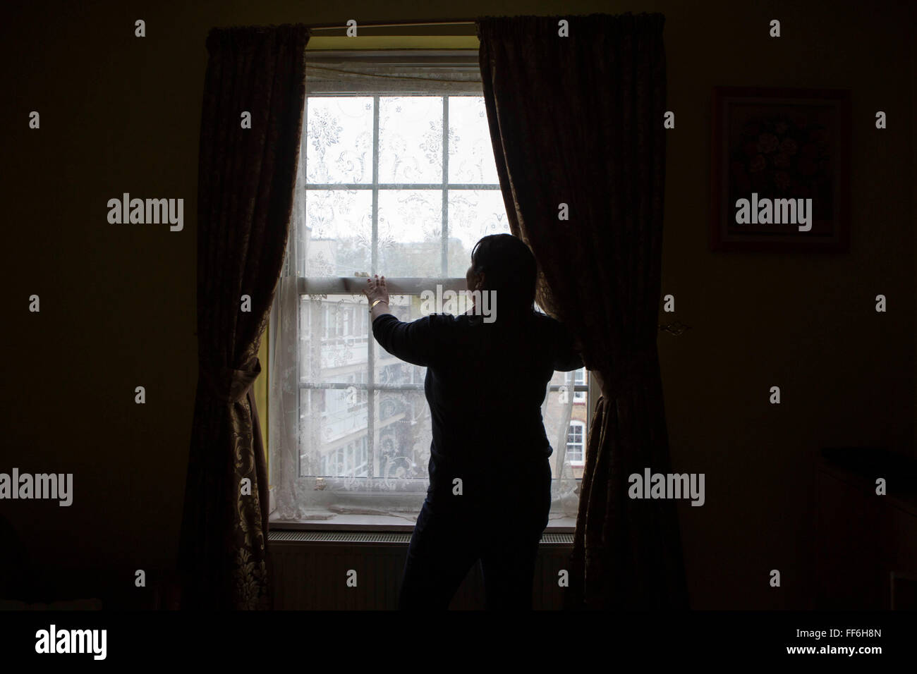 An unidentified lady stands silhouetted in front of her living room window. Isolation and mental health issues in - Stock Image