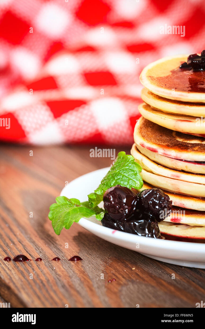 stack of pancakes on a white plate with cherry jam, mint leaves, red checkered napkin, brown wooden background of - Stock Image