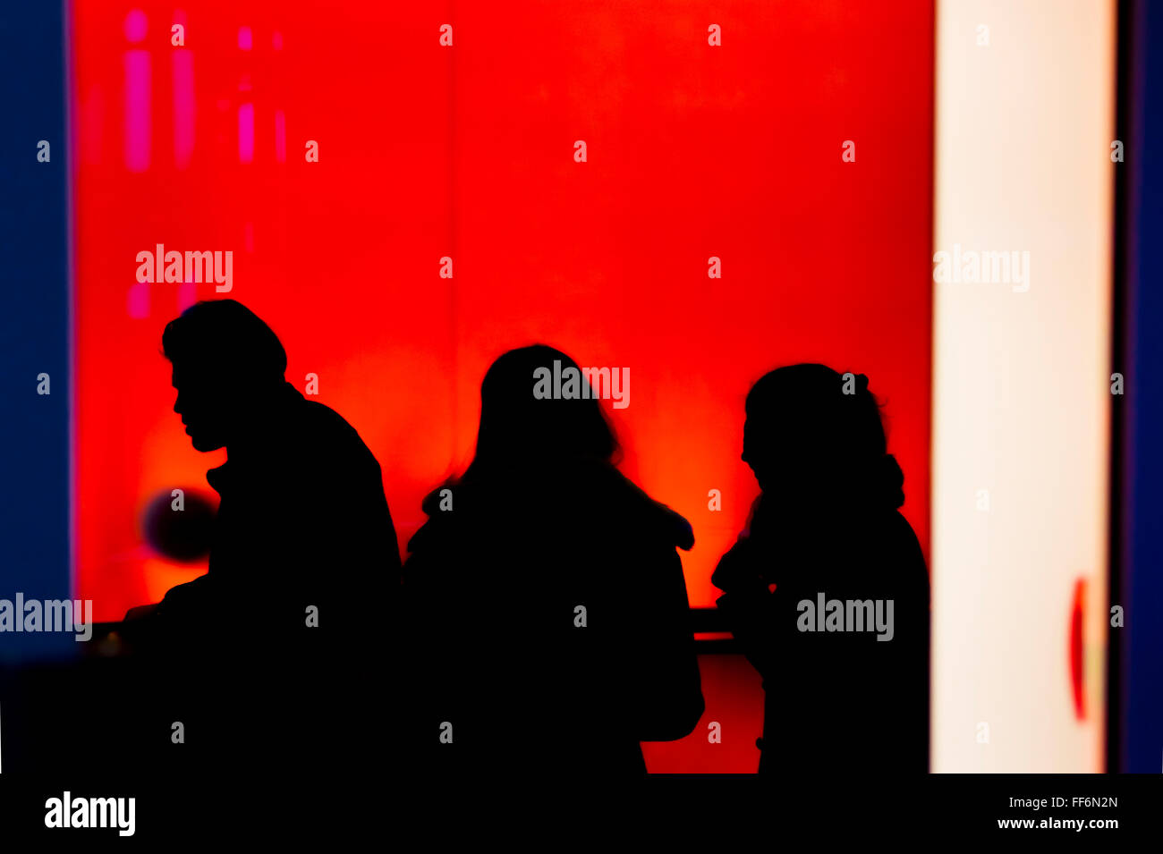 silhouettes of three persons against red background - Stock Image