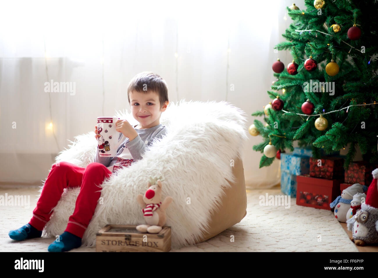 Cute boy, sitting on bean bag, drinking tea and enjoying Christmas holidays, Christmas decoration around him - Stock Image