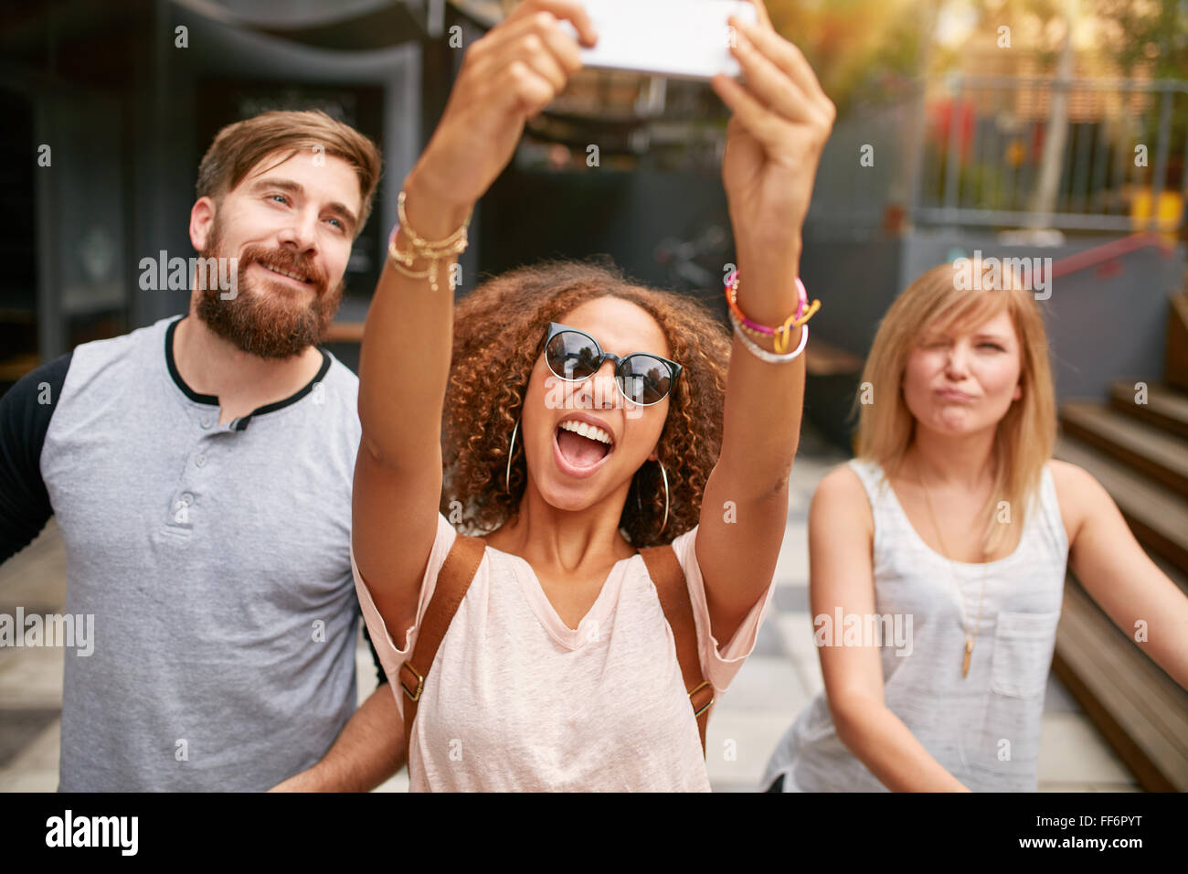Excited young woman with friends taking a selfie on her smart phone. African woman taking selfie with mobile phone. - Stock Image