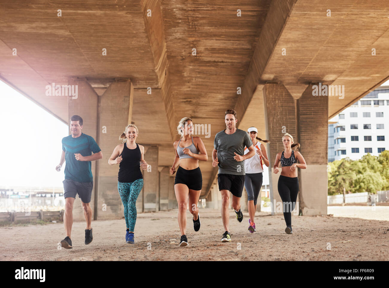 Group of athletes running on a road under bridge in the city. Young men and women jogging, training together in - Stock Image