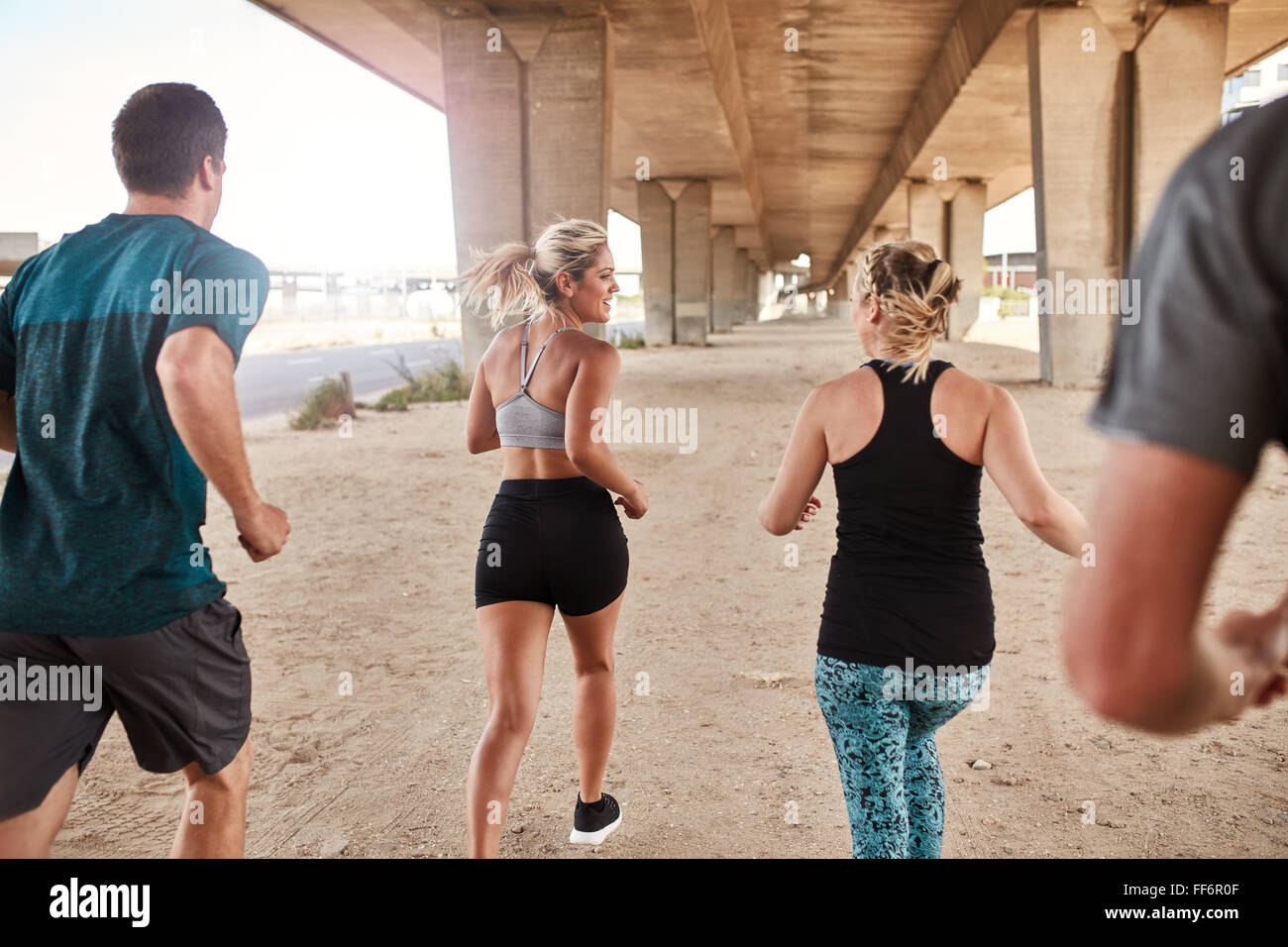 Group of young people working out in the city. Young men and women running under a bridge. - Stock Image