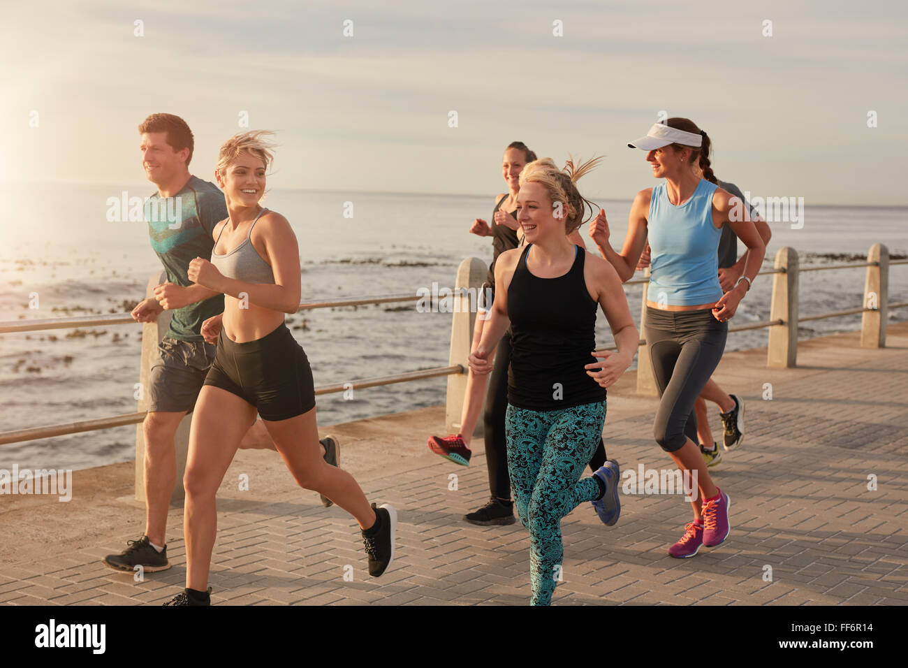 Portrait of young people running by the sea in morning, Healthy young men and women doing running workout. - Stock Image