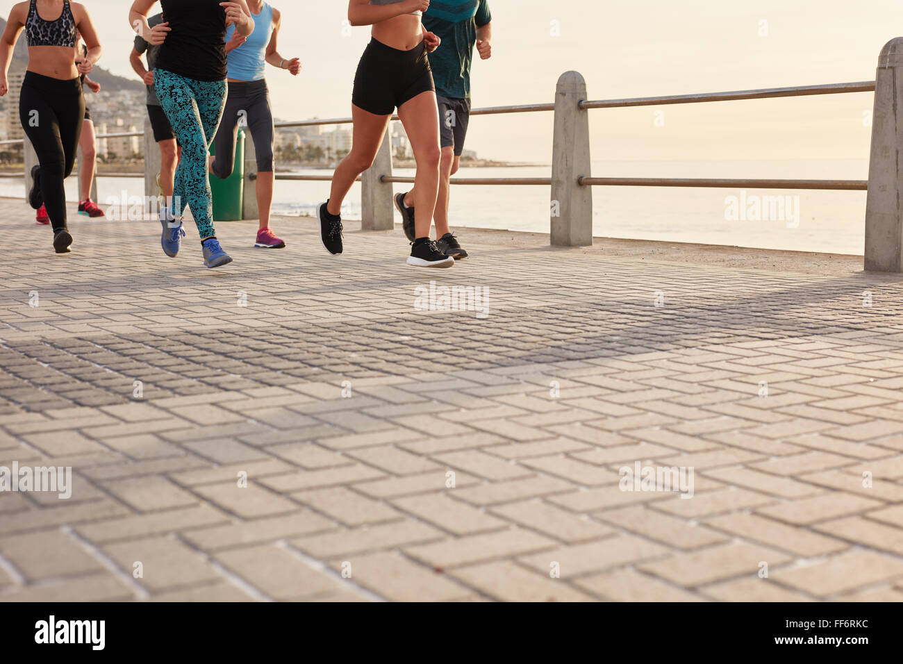 Low section cropped shot of people running on street by the sea. Fitness group training on seaside promenade. - Stock Image