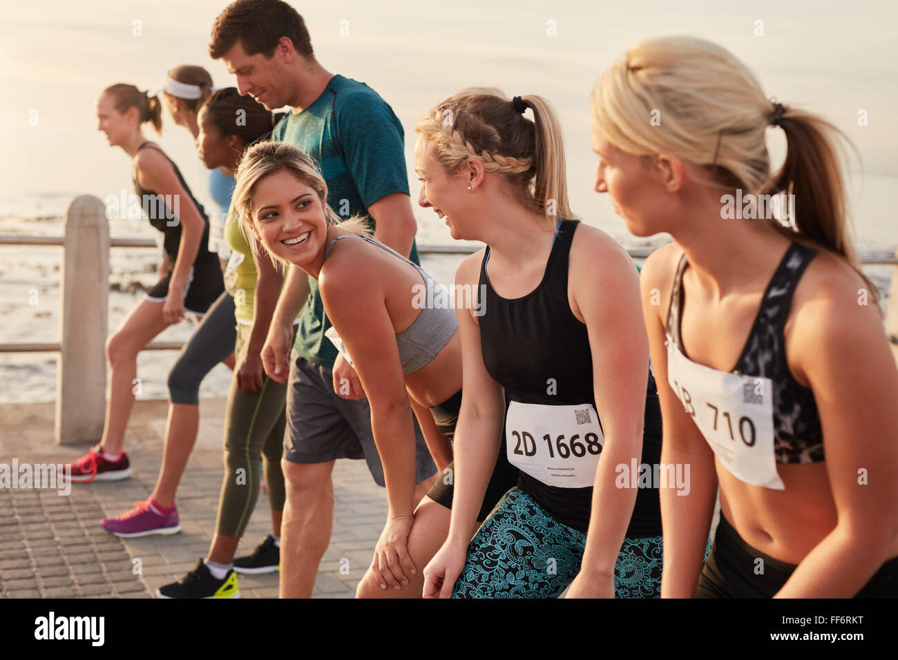Happy young woman standing at starting line along with competitors. Racers standing at starting line of a marathon - Stock Image